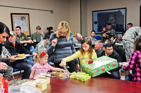 Thea Wendel, wife of Spc. Jason Wendel of Company B, 1st Battalion, 502nd Infantry Regiment, 2nd Brigade Combat Team, 101st Airborne Division (Air Assault) and their children Mason, Audrey and Christian receive presents for Christmas donated by the Occupational Therapy Group from Milligan College at Strike Academy Dec. 15th. The Milligan College campus and its surrounding communities in eastern Tennessee provided the gifts for 89 little Bulldogs. (U.S. Army photo by Sgt. Joe Padula, 2nd BCT PAO, 101st Abn. Div.)