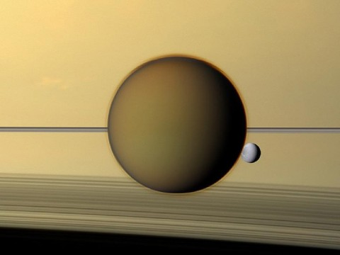 Titan and Dione - Saturn's third-largest moon Dione can be seen through the haze of its largest moon, Titan, in this view of the two posing before the planet and its rings from NASA's Cassini spacecraft. (Image credit: NASA/JPL-Caltech/SSI)