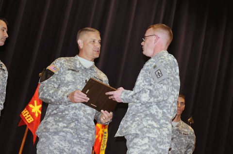 Sgt. Maj. of the Army Raymond Chandler III hands a plaque with the non-commissioned officer creed to the eight air defenders of the 2nd Battalion, 44th Air Defense Artillery Regiment, 101st Sustainment Brigade who were inducted into the NCO Corps at a ceremony, December 2nd. (Photo by Spc. Michael Vanpool)