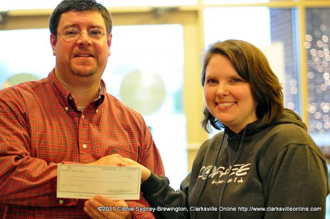 Sango Lasaters manager Megan Ryle presents Lasaters Christmas Giveaway winner Michael Clark with the prize of $1000 in the form of a check Friday, December 23rd.