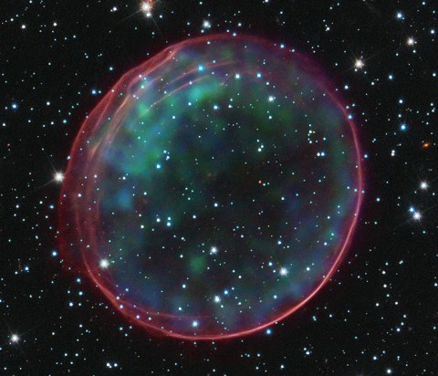 This image of Type Ia Supernova Remnant 0509-67.5 was made by combining data from two of NASA's Great Observatories. The result shows soft green and blue hues of heated material from the X-ray data surrounded by the glowing pink optical shell, which shows the ambient gas being shocked by the expanding blast wave from the supernova. (Image Credit: NASA, ESA, CXC, SAO, the Hubble Heritage Team (STScI/AURA), J. Hughes (Rutgers University))