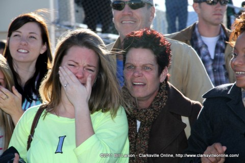 A wife is overcome with emotion as she watches her soldier march by
