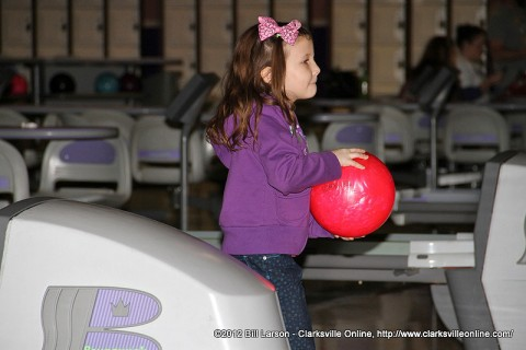 A little girl bowling at the fundraising event at the Pinnacle.