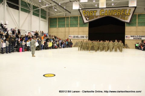 The soldiers march into the hanger as their families cheer loudly for them