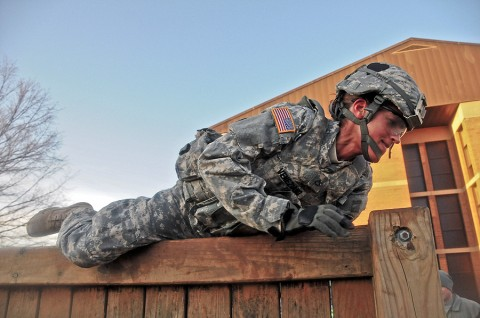 Pfc. Nicole Veneziano, a communications specialist with Headquarters and Headquarters Company, 2nd Brigade Combat Team, 101st Airborne Division (Air Assault), climbs over a six foot wall during a combat focused physical training event honoring Strike's fallen hero Staff Sgt. James P. Hunter, the brigade's combat correspondent who was killed by an IED in southern Afghanistan, June 18th, 2010. Veneziano said that the PT was really demanding and she wanted to quit, but was inspired to continue because of Hunter and his story. (U.S. Army photo by Sgt. Joe Padula, 2nd BCT PAO, 101st Abn. Div.)