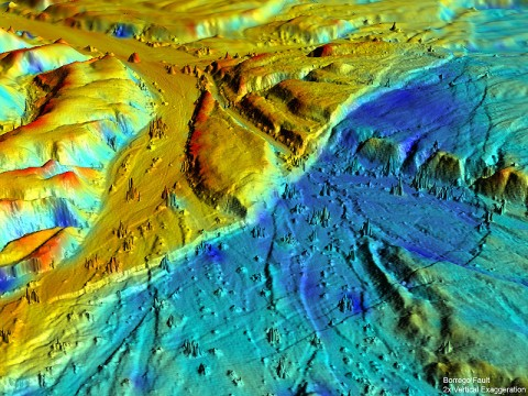 This 3-D airborne light detection and ranging (lidar) oblique view of the Borrego Fault, taken from the post-earthquake topographic survey, shows a wide zone of numerous small faults that slice the ground surface and offset the floor of a desert wash surrounding the main fault. The various colors in the landscape represent elevation changes during the earthquake. Image generated in Crusta (keckcaves.org) with 2x vertical exaggeration. (Image credit: UC Davis)