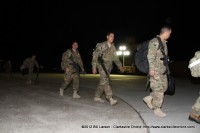 Soldiers look for their family as they head for the hangar