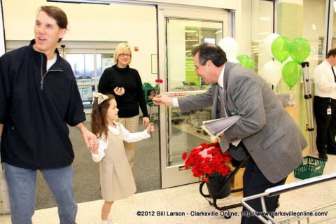 Store manager Norman Rubio Jr. gives a young patron a flower as she enters the store during the grand opening of the Publix store.