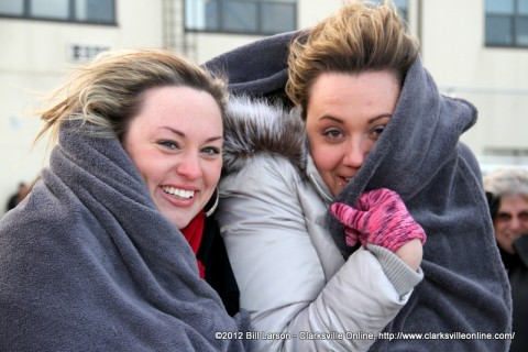 Two women hiding under a blanket from the biting cold as they wait for the flight to land