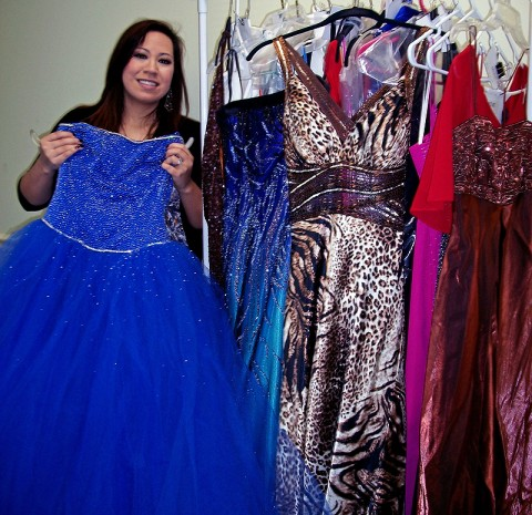 Maria Scott, High School Presenter for Miller-Motte, shows off some of the available dresses at Prom-O-Rama on Saturday. (Photo by: Lois Jones)