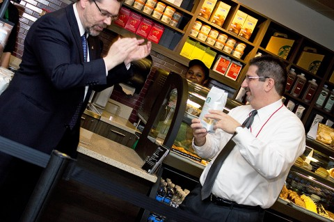 Dr. Tristan Denley, provost and vice president of academic affairs, and Joe Lachina, senior dining services director, cut open a bag of coffee instead of a ribbon at the Starbucks grand opening. (Photo by Amber Fair/APSU)