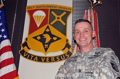 Command Sgt. Maj. David Thompson, command sergeant major of the 101st Sustainment Brigade, stands proudly next to the Designated Unit Insignia he created for the brigade. (Photo by Sgt. 1st Class Peter Mayes)