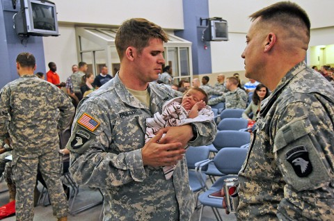 Capt. Daniel Belzer, one of the deploying Security Force Assistance Team members with the 2nd Brigade Combat Team, 101st Airborne Division (Air Assault), holds his newly born child during the brigade's pre-deployment brief held March 6th. The brief provided information and guidance to the family members and Soldiers regarding the upcoming Strike SFAT deployment to Afghanistan. (U.S. Army photo by Sgt. Joe Padula, 2nd BCT PAO, 101st Abn. Div.)
