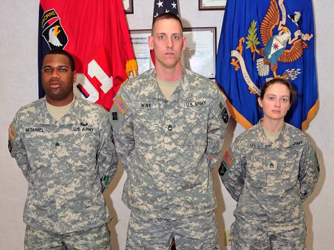 From left to right Sgt. Steve McDaniel and Sgt. 1st Class John Wink, 101st Combat Aviation Brigade electronic warfare non-commissioned officers and Staff Sgt. Mariah Parks, 101st CAB intel analyst stand infront of the brigade colors as the electronic warfare team. (Photo by Sgt. Duncan Brennan)