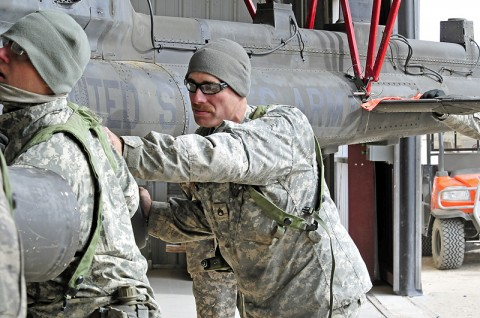 Staff Sgt. Justin Thompson, D Troop, Task Force Saber shops platoon sergeant, helps maneuver a OH-58 Kiowa helicopter inside a hangar at the National Training Center, Fort Irwin, CA, Feb. 15th, 2012. (Photo by Sgt. Tracy Weeden)