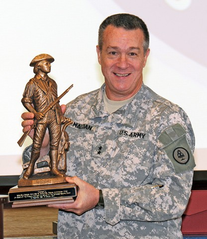 Maj. Gen. William Maloan holds up his Minuteman award during his retirement ceremony.