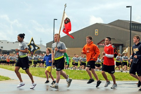 Capt. Alicia Harness, the commander of the Headquarters and Headquarters Company, 101st Special Troops Battalion, 101st Sustainment Brigade, and Spc. Andrew Spencer, the guidon bearer, run with the children of Sgt. 1st Class Charles Adkins, April 16th. The run honored five soldiers of the 101st STB, including Adkins, who were killed during an attack at Forward Operating Base Gamberi, Afghanistan, April 16th, 2011. (Photo by Spc. Michael Vanpool)