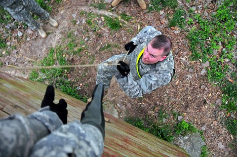 Capt. Gavin Grimm, with the brigade legal office, 2nd Brigade Combat Team, 101st Airborne Division (Air Assault), climbs a ten-foot wall during a 4-mile combat physical training course at Fort Campbell's 'Cav-Country' Mar. 22nd. The Strike Brigade's staff members understand the importance of combat focus training and conduct demanding events on a weekly basis. (U.S. Army photo by Sgt. Joe Padula, 2nd BCT PAO, 101st Abn. Div.)