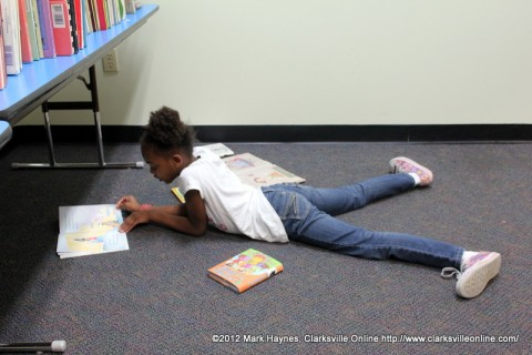 This young lady is enjoying one of her new books in the children's section.