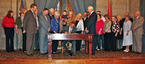 Tennessee Governor Bill Haslam signs Senate Bill 2357 into law as (from left to right) State Representative Joe Pitts, State Senator Tim Barnes and Representative John Tidwell look on. Family members of victims of RV carbon monoxide poisoning joined the Governor and lawmakers for the ceremony.