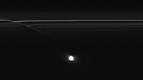 """Images from NASA's Cassini spacecraft: Images from NASA's Cassini spacecraft have revealed half-mile-sized (kilometer-sized) objects punching through parts of Saturn's F ring, leaving glittering trails behind them. These trails in the rings, which scientists are calling """"mini-jets,"""" fill in a missing link in our story of the curious behavior of the F ring."""
