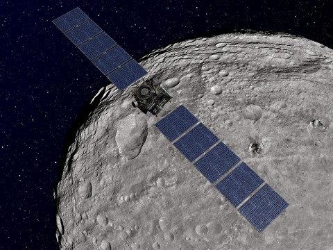 This artist's concept shows NASA's Dawn spacecraft orbiting the giant asteroid Vesta. The depiction of Vesta is based on images obtained by Dawn's framing cameras. (Image credit: NASA/JPL-Caltech)