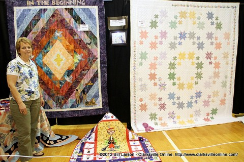 Bea Goddard's daughter stands with some of her mother's quilts