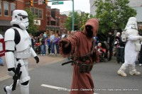 A Tusken Raider from Star Wars is escorted by Storm Troopers