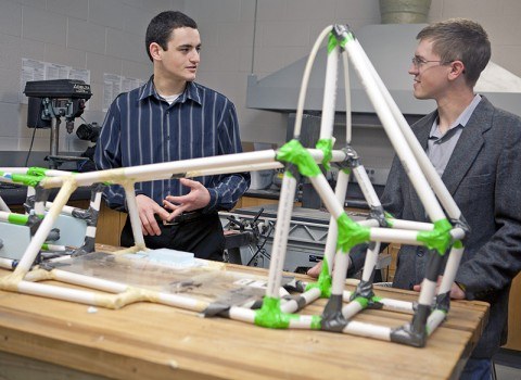 APSU physics students Elijah Jensen and John Walker discuss the half-scale prototype race car frame they designed and built. The next step is to build the full-scale formula SAE racecar. (Photo by Amber Fair/APSU).