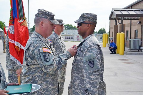 1st Class Alondo Brown receives the Purple Heart from 101st Sustainment Brigade Commander, Col. Michael Peterman, at a special ceremony May 21st, 2012. Brown received the award for injuries he sustained in combat during Operation Iraqi Freedom, in 2006. (U.S. Army photo by Sgt. 1st Class Pete Mayes.)