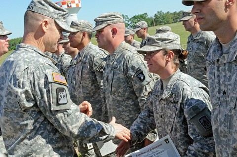 Col. Steven Drennan, commander of the 86th Combat Support Hospital, awards an Expert Field Medical Badge to Sgt. Rachel Barrett, a health care specialist with the 2nd Battalion, 44th Air Defense Artillery Regiment and a native of Murfreesboro, TN, May 11th, 2012 at Fort Campbell, KY. (U.S. Army photo by 101st Sustainment Brigade Public Affairs.)