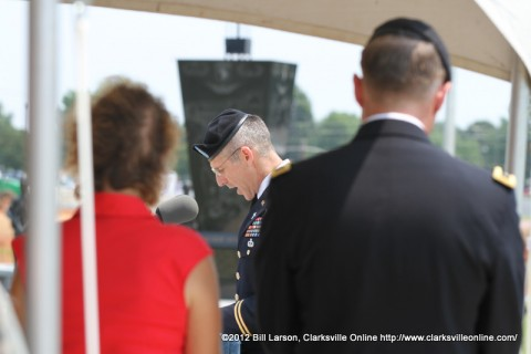Chaplain Paul Hurley gives the invocation as Maj. Gen. James C. McConnell and his wife looks on