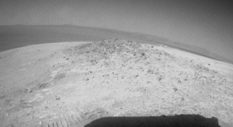 NASA's Mars Exploration Rover Opportunity drove about 12 feet (3.67 meters) on May 8, 2012, after spending 19 weeks working in one place while solar power was too low for driving during the Martian winter. The rover used its rear hazard-avoidance camera after nearly completing the May 8 drive, capturing this view looking back at the Greeley Haven. The dark shape in the foreground is the shadow of Opportunity's solar array. The view is toward the southeast. (Image Credit: NASA/JPL-Caltech)