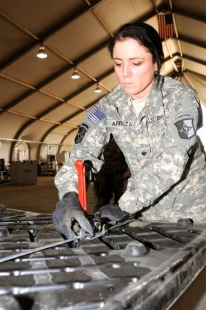 Spc. Sirlen Arriaza, non-rolling stock clerk, 227th Quartermaster Company, from Indianapolis, Ind., secures a pallet of equipment with metal binding strips at the redistribution property assistance team yard on Contingency Operating Base Adder, Nov. 27. (Spc. Anthony Zane/U.S. Army)
