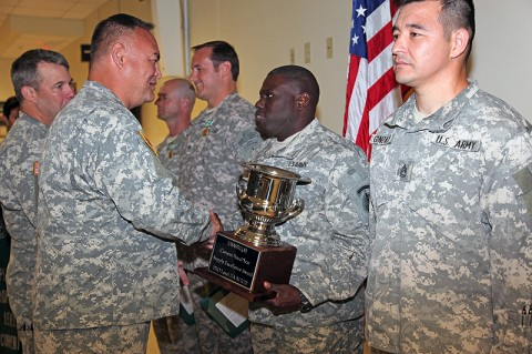 Chief Warrant Officer 3 Truman Mays, Property Book Officer for the 5th Special Forces Group (Airborne), is presented the U.S. Army Special Forces Command Supply Excellence Award by Brig. Gen. Edward M. Reeder, Jr., Commanding General, U.S. Army Special Forces Command, during a ceremony June 26th, 2012, at the 5th SFG (A) headquarters. Mays received the award on behalf of his units' Property Book Office team, who will represent USASFC at the U.S. Army Special Operations Command Supply Excellence Award competition later this month. (Photo by Sgt. Kerry Otjen)