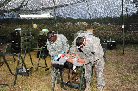 U.S. Army Staff Sgt. Nicholas A. Reasons and Spc. Veronica L. Baldwin, medics from Company C, 801st Brigade Support Battalion, 4th Brigade Combat Team, 101st Airborne Division, treat and stabilize a simulated patient during a mass casualty training exercise June 20th, 2012 at Fort Campbell, KY. (Photo by Staff Sgt. Todd Christopherson)