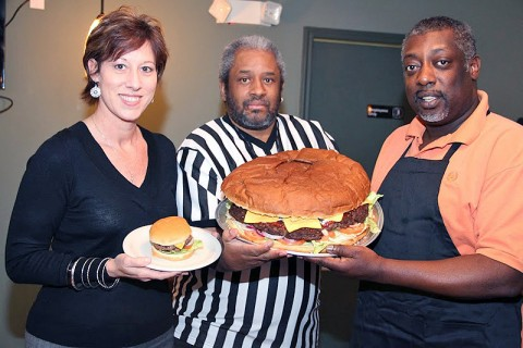 (L to R) G's Pancake House Restaurant owner Cindy Sueiro, Mr. Terry McMoore, and General Manager Anthony Pritchett showing Giant 16 inch 15 Pound Cheese Burger next to a regular size Cheese Burger.