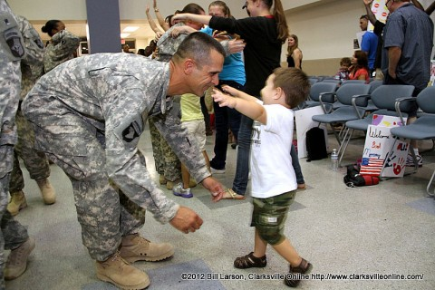 One of the returning soldiers being greeted by his young son on Father's Day