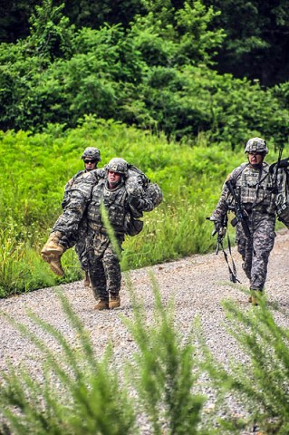 Sgt. James Bradford, an infantryman with Headquarters and Headquarters Company, 1st Battalion, 502nd Infantry Regiment, 2nd Brigade Combat Team, 101st Airborne Division (Air Assault), carries a wounded First Strike Soldier to an evacuation point as Maj. Curtis Rowland, the Strike brigade's executive office, maintains the casualty's weapon during a weekly training exercise called Talon Shock, July 12th held at Fort Campbell, KY. (U.S. Army photo by Sgt. Joe Padula, 2nd BCT PAO, 101st Abn. Div.)