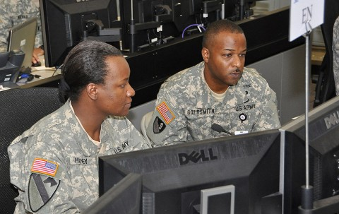 Maj. Julia Harvey and Chief Warrant Officer 4 Dominic Goldsmith, both with the III Corps Engineer Office, review activity from their work station in the corps' tactical operations center at Fort Hood, Texas, June 15th, 2012. The pair of two of more than 5,500 service members taking part in the III Corps Warfighter Exercise, expected to conclude June 22nd. (Photo Credit: Dave Larsen, III Corps Public Affairs)