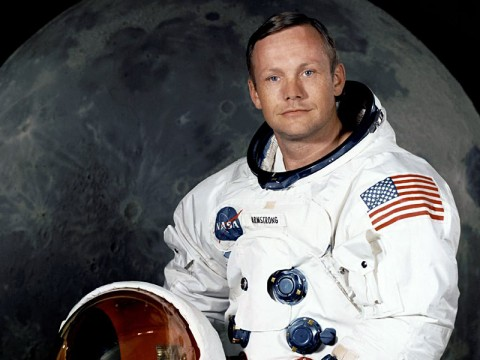 Portrait of Astronaut Neil A. Armstrong, commander of the Apollo 11 Lunar Landing mission in his space suit, with his helmet on the table in front of him. Behind him is a large photograph of the lunar surface. (Image Credit: NASA)