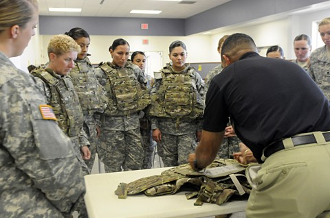 The Female Engagement Team from the 1st Brigade Combat Team, 101st Airborne Division, gather as an instructor explains how to use the Generation III Improved Outer Tactical Vest August 21st at the PPC here. (Photo by Spc. Kadina Baldwin)