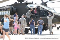 A young girl gets a moment in the pilots seat in a Boeing AH-64 Apache helicopter
