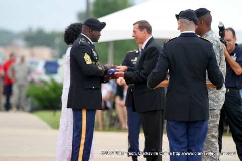 Gen. David H. Petraeus (U.S. Army Ret) presents a flag that flew over the 101st Airborne Division headquarters to Command Sergeant Major Marvin L. Hill  at his retirement ceremony