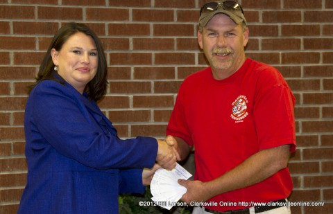 Amy Carroll of Big Brothers, Big Sisters of Clarksville receiving 70 Tickets to a fundraising concert featuring John Michael Montgomery from  David Kirkland, the president of Clarksville Firefighters Local 3180