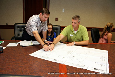 J. Lee Powell and Jon Vaughn of Better Homes and Garden Hometown Connection Real Estate look at maps showing the location of the property he donated.