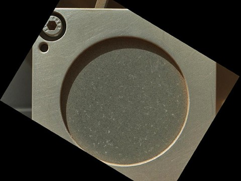 A sample of basaltic rock from a lava flow in New Mexico serves as a calibration target carried on the front of NASA's Mars rover Curiosity for the rover's Canadian-made Alpha Particle X-Ray Spectrometer (APXS) instrument. (Image credit: NASA/JPL-Caltech/Malin Space Science Systems)