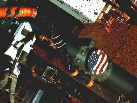 """This view of the American flag medallion on NASA's Mars rover Curiosity was taken by the rover's Mars Hand Lens Imager (MAHLI) during the 44th Martian day, or sol, of Curiosity's work on Mars (September 19th, 2012). The flag is one of four """"mobility logos"""" placed on the rover's mobility rocker arms."""