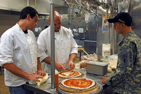 "The Blackhorse Pub and Brewery chefs Brandon Crotzer and Zachary Matthews give tips on cooking pizza ""Blackhorse Style"" to Oasis Dining Facility cook Pfc. Robert Archuleta. (5th Special Forces Group (Airborne) Public Affairs)"