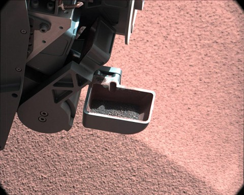 In this image, the scoop on NASA's Curiosity rover shows the larger soil particles that were too big to filter through a sample-processing sieve that is porous only to particles less than 0.006 inches (150 microns) across. (Image credit: NASA/JPL-Caltech/MSSS)